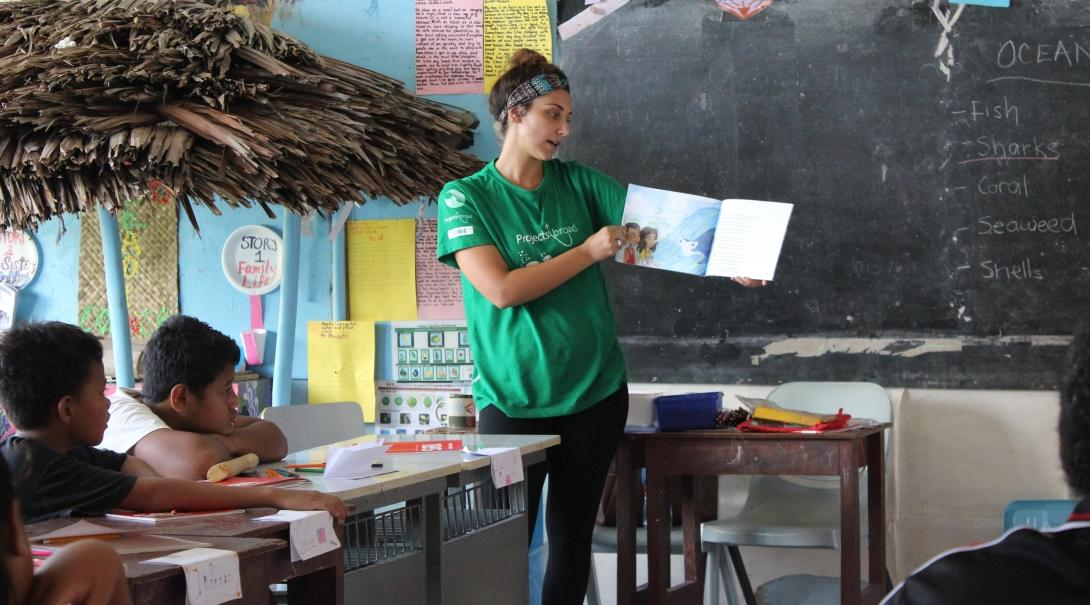 An alternative schoolies volunteer in Samoa reads a book for a class
